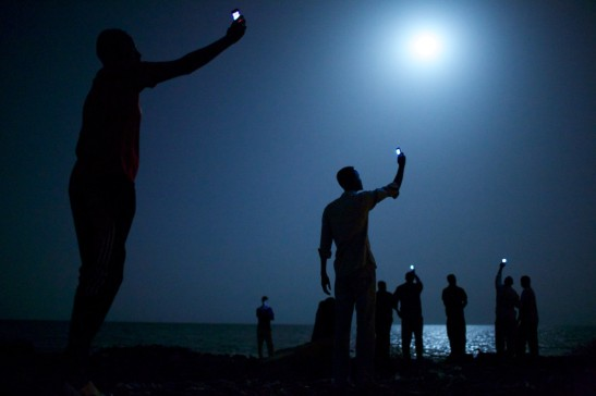 World Press - Fotografia anului 2013: 26 Februarie 2013, Djibouti. Emigranți africani, ajunși noaptea la marginea orașului Djibouti, ridicându-și telefoanele în încercarea de a prinde un semnal ieftin din ara vecină, Somalia - o cât de mică legătură cu rudele rămase acasă. Djibouti este o escală comună pentru emigranții din Somalia, Etiopia sau Eritreeea, aflați în tranzit spre o viață mai bună în Europa sau Orientul Mijlociu. © John Stanmeyer, USA, VII for National Geographic